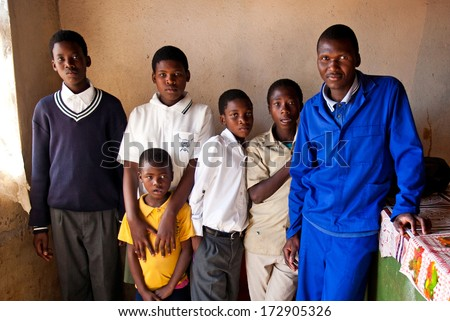 MBABANE, SWAZILAND - AUGUST 5: Unidentified orphan Swazi children with a man on August 5, 2008 in Mbabane, Swaziland. Close to 10 percent of Swaziland's total population are orphans, due to HIV/AIDS. - stock photo