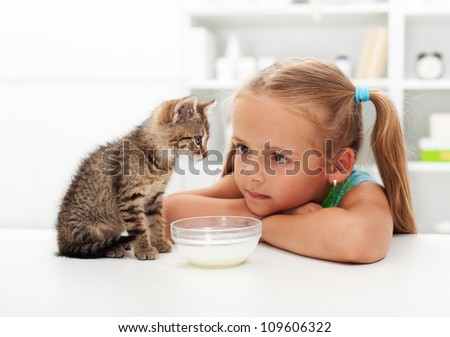 Me and my cat - little girl and her new kitten getting to know each other - stock photo