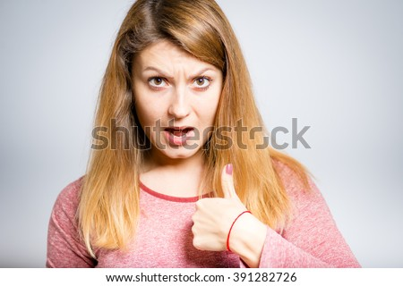 Me? Portrait of a young angry woman is pointing the finger herself, isolated on a gray background