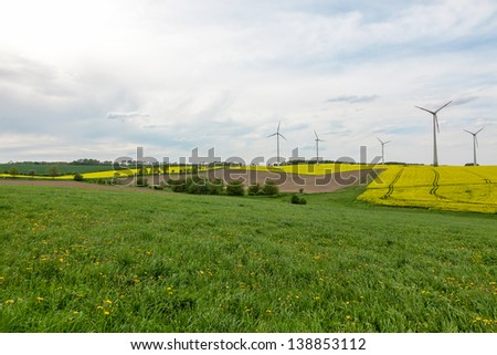 Meadows and fields with wind turbines - stock photo