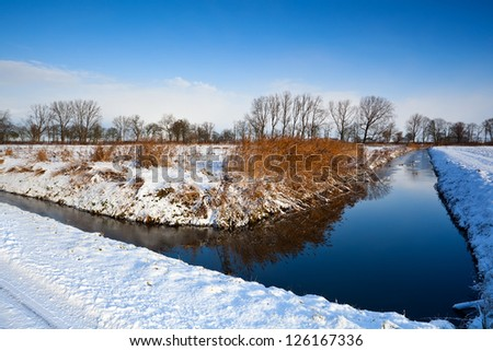 meadows in snow and canal during winter - stock photo