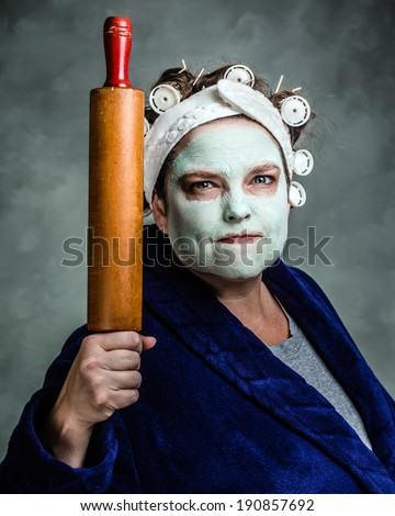 Mean and ugly housewife with facial mask, hair rollers and rolling pin - stock photo