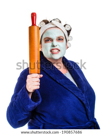 Mean and ugly housewife with facial mask, hair rollers and rolling pin isolated on white - stock photo