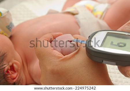 Measure child glucose level blood test diabetes new born baby  using glucometer - stock photo