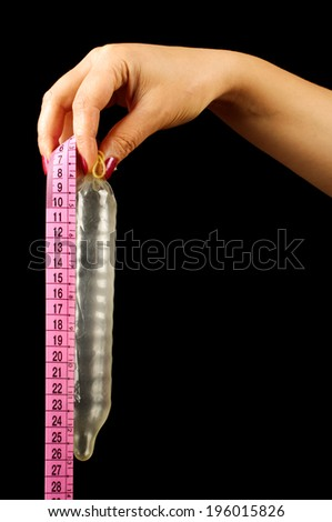 Measure size of the condom female hand on the black background - stock photo