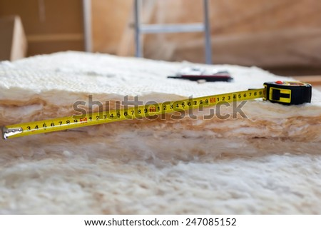 Measure tape and knife on mineral wool, closeup  - stock photo
