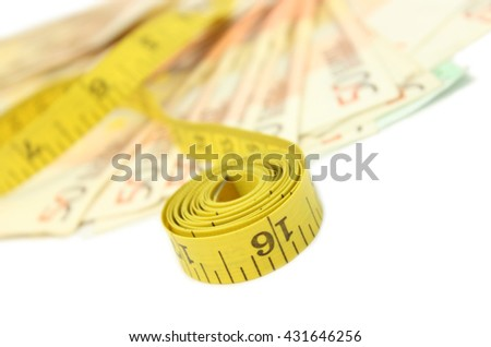 Measure tape and money - stock photo