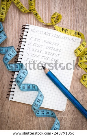 Measure tape and  notepad with New Year's resolutions - stock photo
