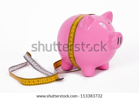 Measure tape and pink piggy bank, isolated on white background. - stock photo