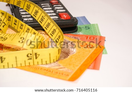 Measure tape, calculator and Malaysian bank notes. Tailor and fashion symbolic.
