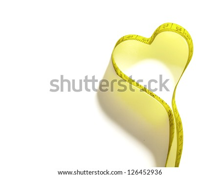 Measure tape heart shaped. Isolated over white. Yellow measuring tape isolated on white background - stock photo