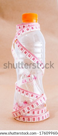 Measure tape wrapped around a bottle of water isolated on brown - stock photo