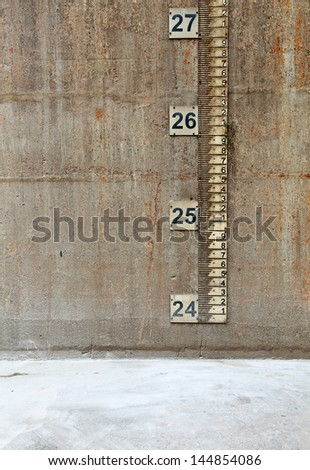 Measurement dipstick on the concrete wall of an empty water reservoir tank.   - stock photo
