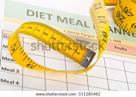 Measurement tape on diet meal planner sheet - dieting or weight loss concept