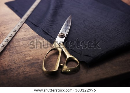 Measuring and cutting textile or fine cloth. Work table of a tailor. Gold scissors and black silky fabric. Intentionally shot in retro muted color. - stock photo