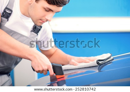 Measuring coating thickness. Closeup of a handsome car mechanic checking the thickness of car coating with a special electronic tool and cleaning it with wiper in car repair shop - stock photo
