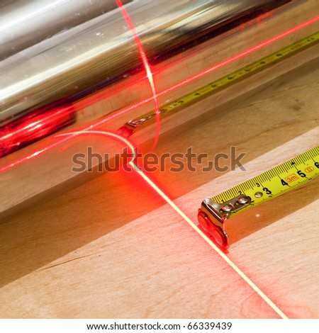 Measuring concept with tape measuring tool and red laser beam - stock photo