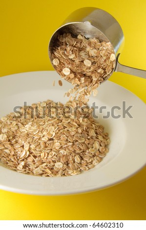 Measuring cup pouring organic cereal on white plate over colorful yellow background - stock photo