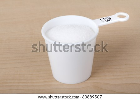 Measuring cup with one cup of sugar - stock photo