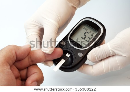 measuring glucose level with a digital glucose meter. concept of diabetics checking level sugar. - stock photo
