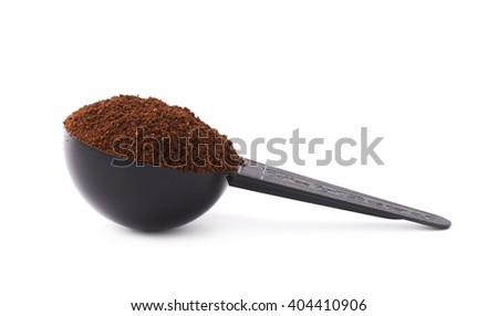 Measuring little spoon filled with coffee over isolated white background - stock photo