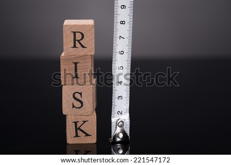 Measuring risks with ruler over black background - stock photo