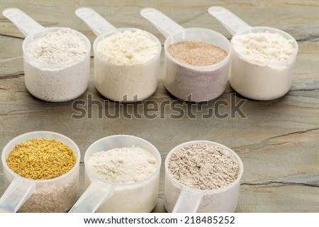 measuring scoops of gluten free flours - almond, coconut, teff, flaxseed meal, whole rice, brown rice, buckwheat, slate rock background - stock photo