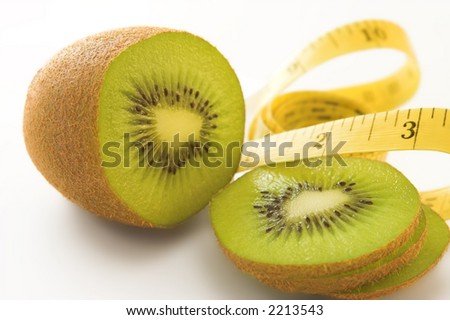 Measuring tape and a kiwifruit against a white background. Shallow D.O.F. - stock photo