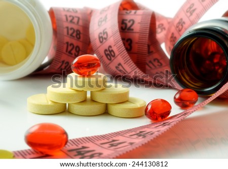 Measuring tape and bottle with pills. supplements for weight loss - stock photo
