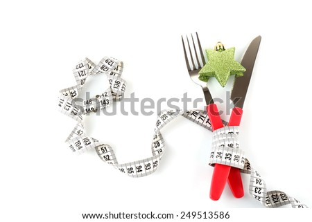 Measuring tape and cutlery with Christmas decoration isolated on white - stock photo