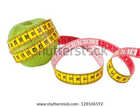 Measuring tape and fresh green apple on a white background