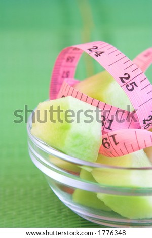 Measuring tape and fruit in a glass bowl against a green background.  Shallow D.O.F ? some of the measuring tape, fruit and bowl in focus ? background completely out of focus. - stock photo