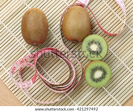 Measuring tape and kiwi fruit, kiwi fruit diet concepts,weight loss.View from the top. - stock photo