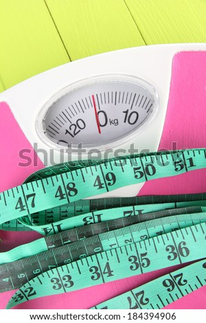 Measuring tape and scales close-up on wooden table - stock photo