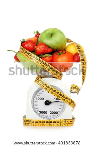 measuring tape around scales with fruits and vegetables, dieting concept - stock photo