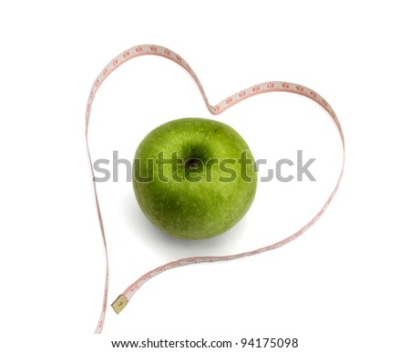Measuring tape looking as heart and green apple,isolated over white background - stock photo