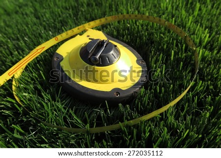 Measuring tape lying on the fresh mow lawn grass in the summer garden - stock photo