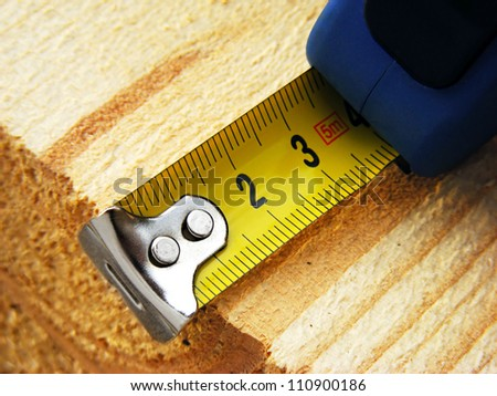 Measuring tape on a wood plank. Build concept. - stock photo