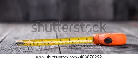 Measuring tape on a wooden board with copyspace