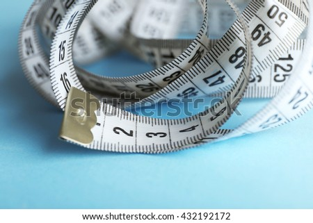 Measuring tape  on blue background - stock photo