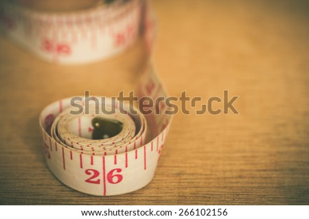 measuring tape on wooden background ,vintage color tone. - stock photo