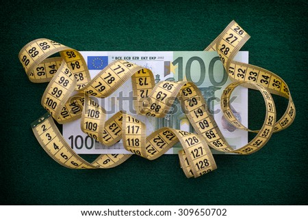 Measuring tape over one hundred euro note on green background. Close up. - stock photo