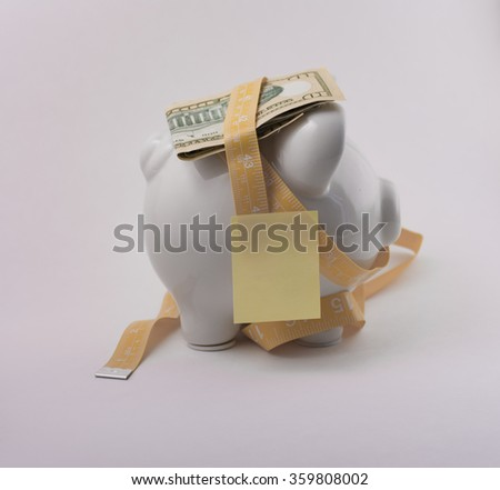 Measuring tape surrounding piggy bank with reminder note. - stock photo