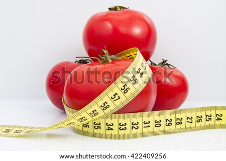 Measuring tape with tomato isolated on white background. - stock photo