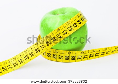 Measuring tape wrapped around a green apple .Concept symbol of diet. Isolated on white background.