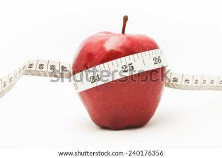 Measuring tape wrapped around a red apple as a symbol of diet.
