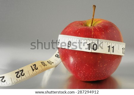 Measuring Tape Wrapped Around a Red Apple as a Symbol of Diet - stock photo