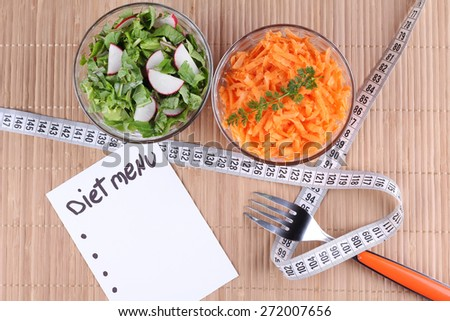Measuring tape wrapped around the fork. Vegetable salad, radish salad and spinach, carrot salad. Glass bowls. Diet menu, diet. Dietary food. - stock photo