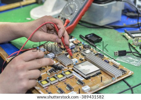 Measuring the electronic components on the motherboard of the computer - stock photo