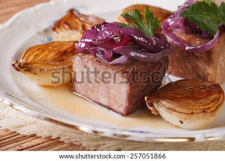 Meat and caramelized onions on a white plate close-up. horizontal - stock photo